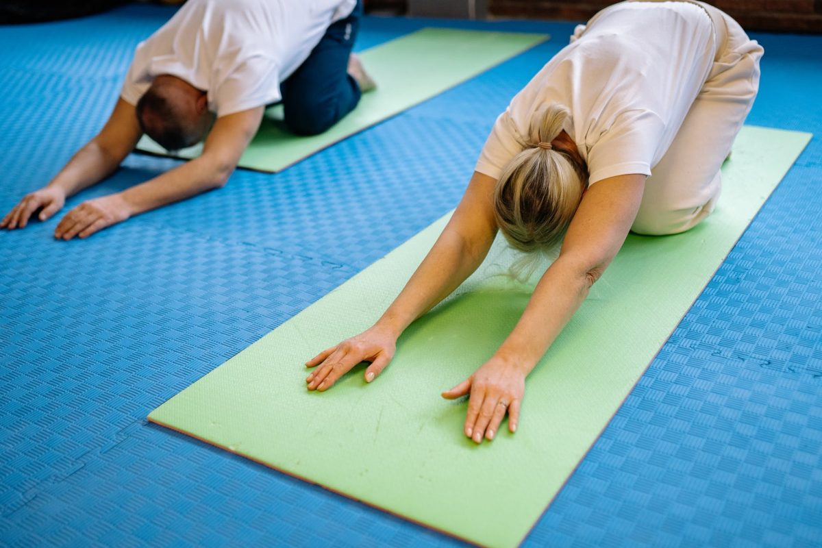 a couple in the gym doing yoga pose